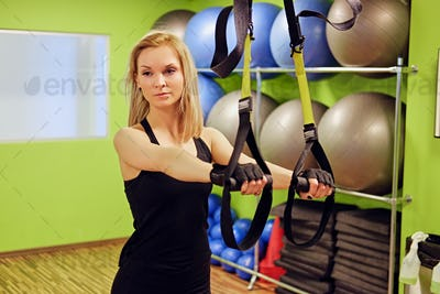 Slim female doing trx straps exercises in a gym.