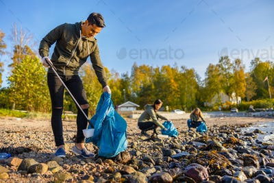 Man cleaning beach with volunteers on sunny day