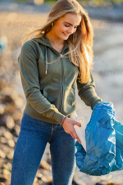 Smiling Young Female Volunteer holding bottle and garbage bag at beach