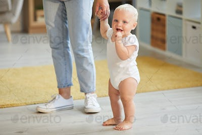 Baby And Mom Holding Hands To Walk