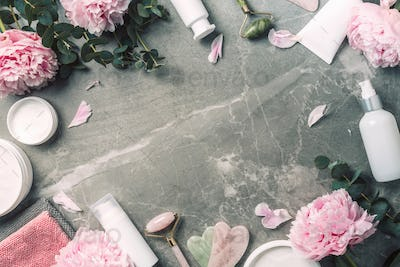 Cosmetic products bottles, towels, oil, face roller and gua sha massager, pink peonies flowers on