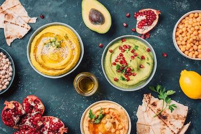 Bowls with yellow hummus and green hummus, tahini, olive oil, sesame seeds, pita, raw chickpeas