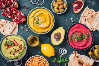 Colorful hummus bowls - green, yellow and beetroot hummus on dark background with lemon, olive oil