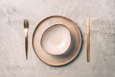 Stoneware plate setting with knife and fork on marble background. Top view. Copy space. Flat lay