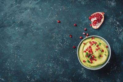 Homemade green hummus with avocado, parsley, olive oil, pita, raw chickpeas, pomegranate on dark