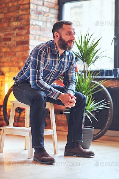 A bearded hipster male dressed in a fleece shirt sits on a wooden chair.