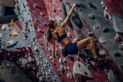 Free climber female bouldering indoors.