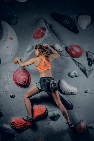 Sporty female climbing on an indoor climbing wall.