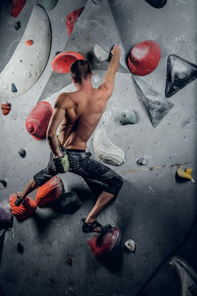A man climbing on an indoor climbing wall.