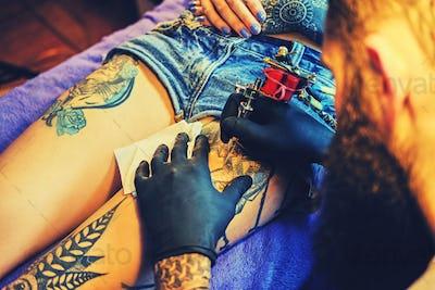 Bearded tattoo male artist makes a tattoo on a female leg.