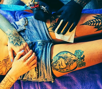 Close up image of making a tattoo on a woman's leg.