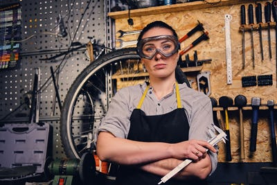 Female bicycle mechanic over tool stand background.