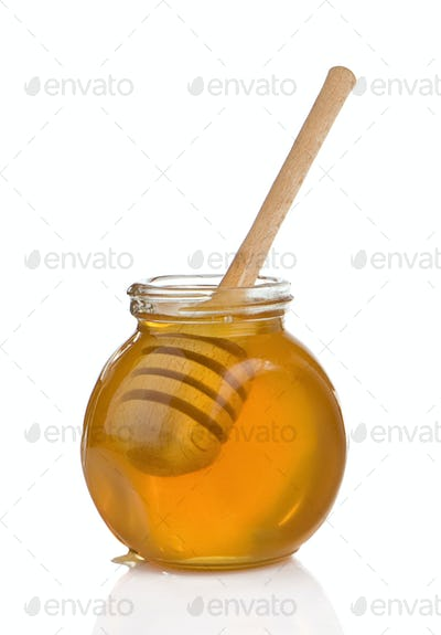 glass pot full of honey and stick isolated on white