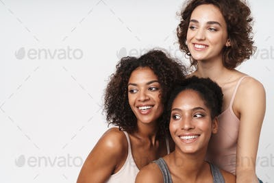 Portrait of three cheerful multiracial women smiling and looking aside
