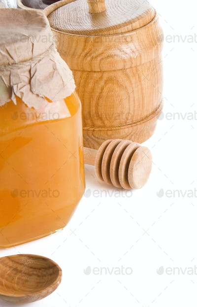 glass and wood jars of honey isolated on white