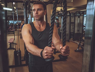 Muscular man doing triceps exercise.