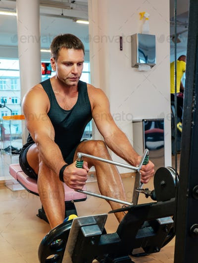 Middle age man doing workouts in a gym club.