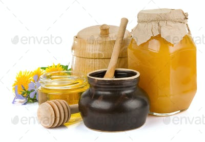 jar of honey and flowers isolated on white