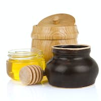 jars and pot of honey isolated on white