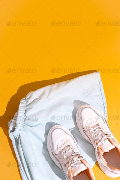 Clothing flat lay summer outfit fashion. Stylish white sneakers. Pastel colours trends aesthetics