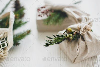 Stylish christmas gifts wrapped in linen fabric with green branch