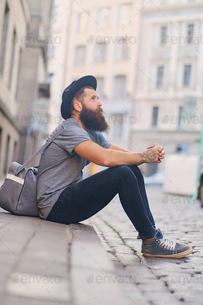 Casual bearded hipster sits on a step on a street.