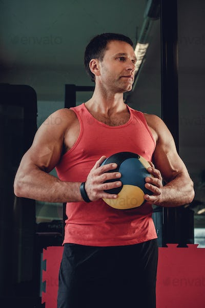 Muscualr man in a red t shirt holds a ball.