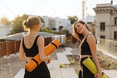 Two young beautiful women in sportswear going to do sports training, gymnastics, yoga