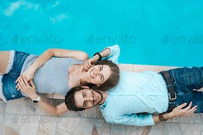 Love couple lying near swimming pool