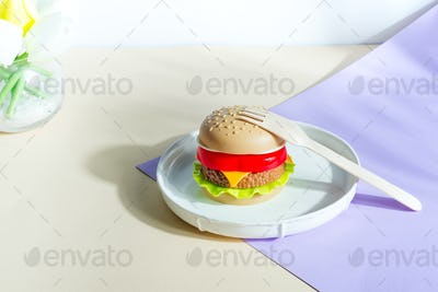 Plastic hamburger on a plate with wooden fork. Dinner set