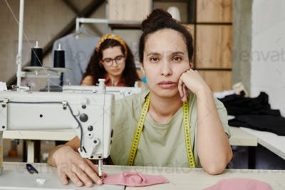 Young tired or bored seamstress with measuring tape on her neck looking at you