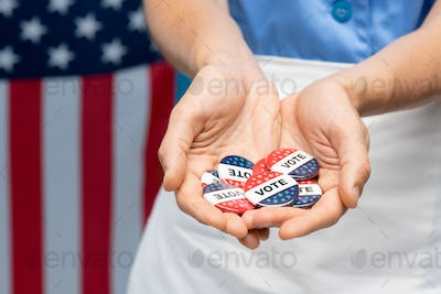 Hand of young chambermaid in uniform or housewife showing you vote insignias