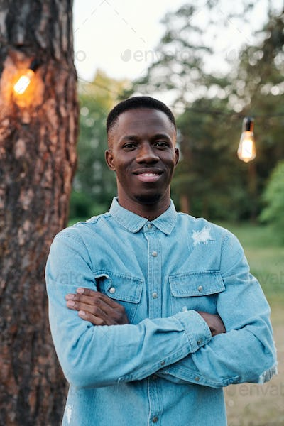 Young cheerful man of African ethnicity in denim shirt keeping his arms crossed
