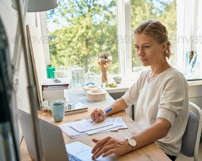 Young female entrepreneur designer writing on paper sheet, serious woman thinking and planning