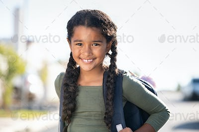 Smiling elementary school girl with bagpack
