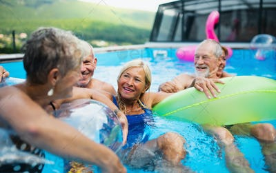 Group of cheerful seniors in swimming pool outdoors in backyard, talking