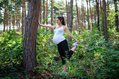 Portrait of happy pregnant woman outdoors in nature, doing exercise