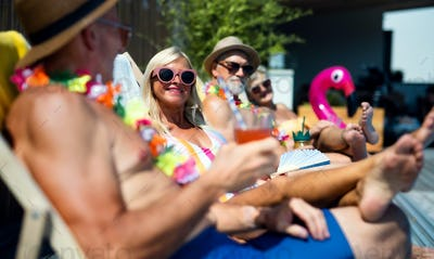 Group of cheerful seniors sitting by swimming pool outdoors in backyard, party concept