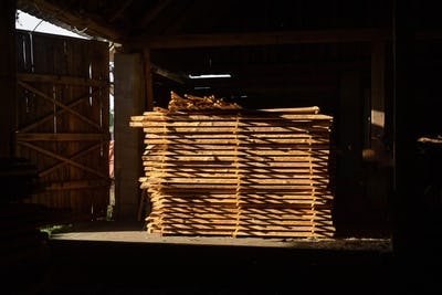 Stack of cut wooden boards at woodworker workshop