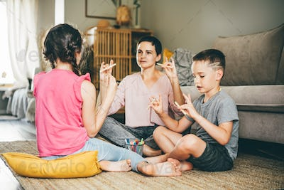 mother with little son and daughter does developing exercises for fingers with wooden pencils
