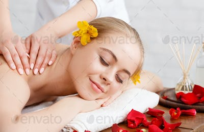Relax and beauty care. Smiling girl lies on massage table with flower petals