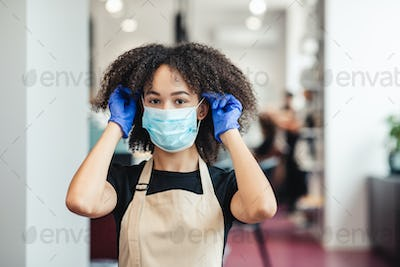 Beauty master putting on protective medical mask before work in salon