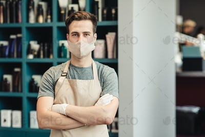 Portrait of confident barber posing in protective mask and apron in beauty salon interior, empty