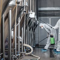 Craft brewery, eco product and disinfection. Workers in hazmat suits clean plant