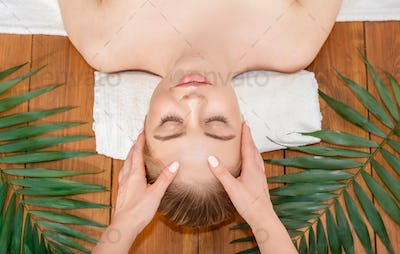 Cosmetology and facial massage in spa. Girl lies on table on white towel with palm leaves