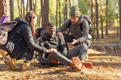 Friends helping african injured guy while hiking by forest
