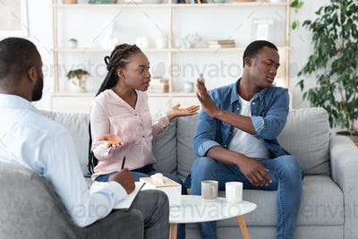Black couple arguing in front of their therapist at session in office