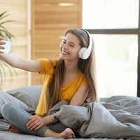 Happy young girl in headphones taking selfie with mobile device on bed at home