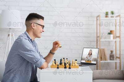 Online meeting and hobby in self-isolation. Guy plays chess at home and looks at laptop
