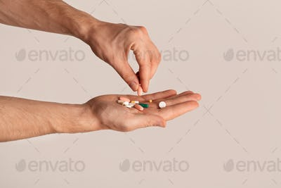 Cropped view of young guy holding pile of pills over light background, closeup